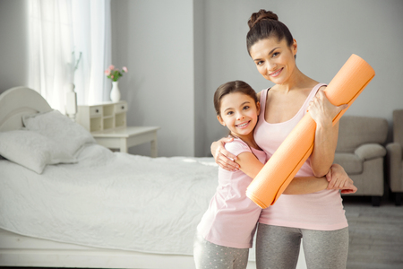 I treasure you. Beautiful cheerful young dark-haired mother holding a carpet and hugging her daughter and they wearing sports clothes Stock Photo