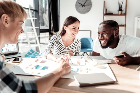 Professional communication. Joyful nice happy colleagues smiling and talking to each other while working together Stock Photo