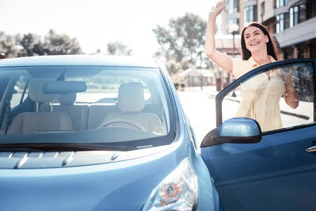 Hey its me. Satisfied pleasant cute woman standing on the street near the car opening the door of the car holding hand up. Stockfoto
