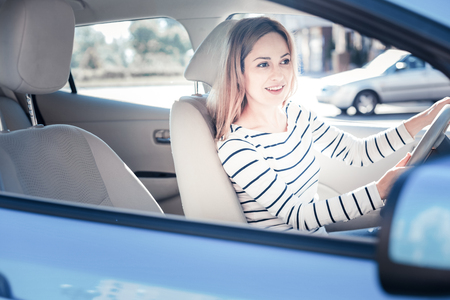 Lets go. Satisfied cute pleasant woman holding by the helm smiling and riding in the car. Stockfoto