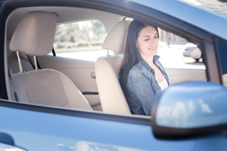Be attentive. Pleasant pretty joyful woman smiling and looking down sitting in the car.