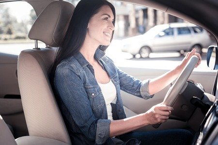 Lets drive. Joyful confident responsible woman sitting in the car holding by the helm and smiling.
