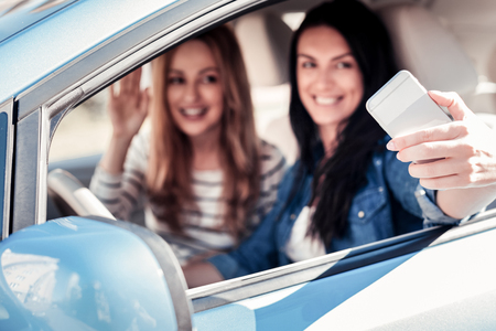Lets do a selfie. Satisfied pleasant friendly women sitting in the car smiling and making photo on the smartphone.