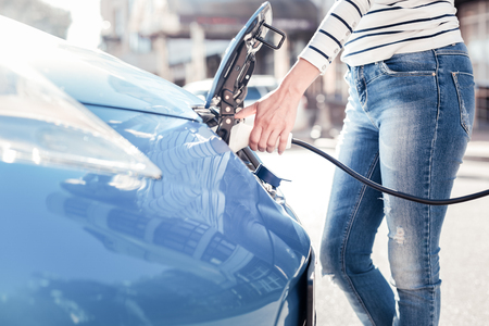 Need to charge. Responsible calm young woman standing near her car holding and using charging gadget. Stockfoto