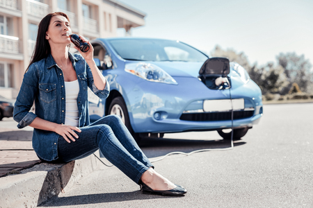 So hot. Young cute pleasant woman charging the electric car drinking water on the board and looking aside.