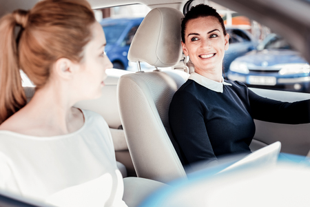 Everything will be fine. Joyful cute stylish woman sitting in the car holding by the helm and smiling.