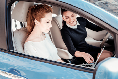 I will help you. Occupied serious smart woman sitting in the car using the laptop and listening to her friend advices. Stockfoto
