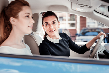 Which the way. Interested pleasant stylish woman sitting in the car looking at her friend and smiling.