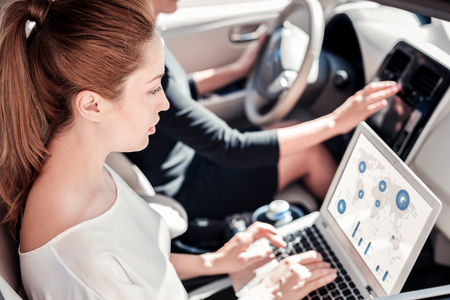 Check the statistic. Busy smart confident woman working with the laptop being in car and sitting near her friend.