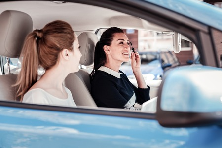 Beauty above everything. Fashionable satisfied friendly woman sitting in the car near her friend sprucing and being in the mirror.