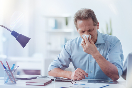 Having a cold. Nice cheerless adult man holding a paper tissue and using it while having a running nose
