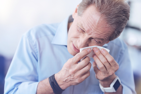 Stopping tears. Cheerless unhappy adult man holding a paper tissue and wiping his eyes while having an allergic reaction