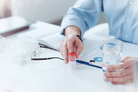 Gebrauchsfertig. Flasche Medizin auf dem Tisch stehend und von einem netten erwachsenen Mann gebrauchsfertig Standard-Bild - 96937168