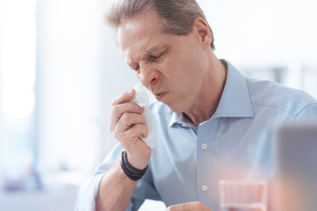 Seasonal Allergy Cheerless Unhappy Nice Man Holding A Paper Tissue And Wiping His Nose While