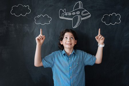 Lets fly. Excited cheerful little boy pointing to the sky while dreaming of travelling by plane Banco de Imagens