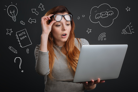 Surprised woman. Curious emotional student putting her glasses up on the forehead and feeling surprised while looking at the screen of her modern laptop Stock Photo