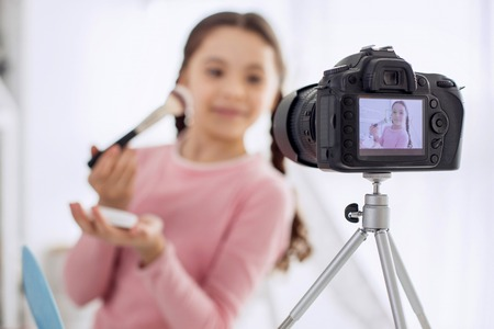Professional approach. New high-quality camera standing on a tripod and filming a charming pre-teen girl conducting makeup tutorial and applying powder to her face