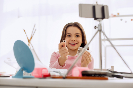 Useful accessory. Adorable pre-teen girl smiling at the camera while talking about hair ties and filming it for her beauty blog Stockfoto