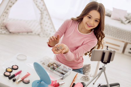 Vast choice. Sweet pre-teen girl sitting at the table and showing a handful of hair ties to the camera of her phone while filming a tutorial