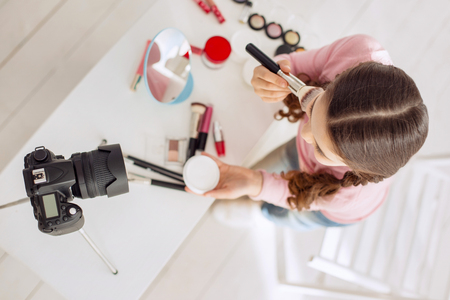 Love blogging. The top view of a cute pretty girl applying powder to her cheekbones while telling her viewers the correct algorithm Stock fotó