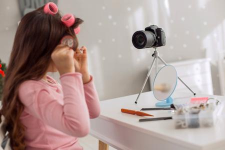 Słodka fryzura. Ładna nastolatka w różowym swetrze, siedząca przy stole, używająca wałków do włosów i nagrywająca samouczek wideo swoim aparatem