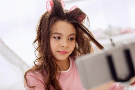 Boucles magnifiques. Jolie fille préadolescente bouclant ses cheveux à l'aide de rouleaux de cheveux et les enregistrant sur son téléphone, sur le point de publier un didacticiel vidéo Banque d'images