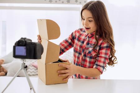 Aangename verrassing. Charmant pre-tienermeisje dat een doos opent en naar adem snakt terwijl ze de inhoud van de doos ziet terwijl ze een unboxing-vlog opneemt