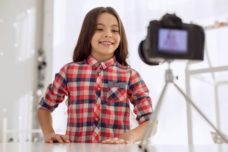 Charming smile. Joyful pre-teen girl in a checked shirt posing for the camera and smiling at it while recording a video blog