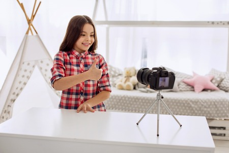 Best mood. Pretty pre-teen girl in a checked shirt filming a video blog and showing a thumbs up while recording a video blog