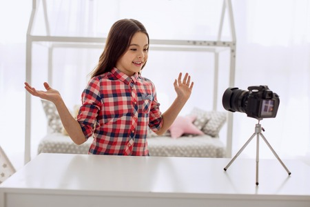 Pleasant contact. Adorable pre-teen girl talking to her audience and telling about her day while recording it with the help of a camera Reklamní fotografie