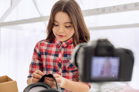 Vital advice. Lovely pre-teen girl showing how to regulate VR headset straps and recording it on the camera, making a video tutorial for her blog