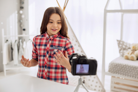 Pleasant interaction. Cheerful pre-teen girl recording a video blog and answering the questions of her audience in it while gesticulating