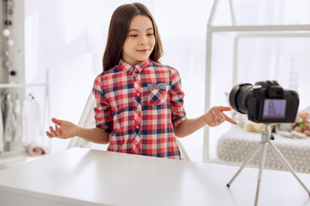 Interesting story. Happy pre-teen girl in a checked shirt filming a video blog and telling her viewers about her day while gesticulating