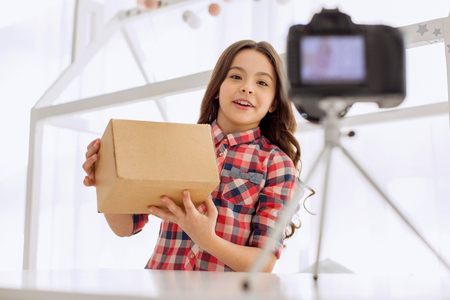 Popular video genre. Sweet pre-teen girl in a checked shirt holding a box in her hands and smiling cheerfully while recording an unboxing video on the camera
