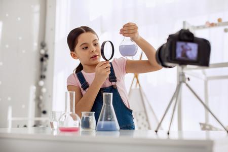 Getalenteerde chemicus. Mooi pre-tienermeisje dat door een vergrootglas naar een fles met een chemische stof erin kijkt terwijl ze zichzelf opneemt voor een videoblog