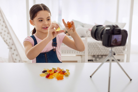 Love sweets. Pleasant cute pre-teen girl holding two gummy bears and reviewing them on camera while recording a video blog