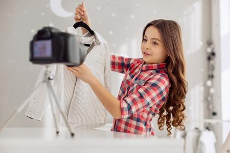 Mooi kledingstuk. Leuk pre-tienermeisje met krullend haar dat een videoblog filmt en vertelt over haar nieuwe shirt erin, sprekend over de kwaliteit ervan Stockfoto