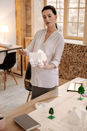 Ideal house. Professional focused pregnant designer estimating house model while holding it and staying at office Stock Photo