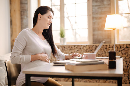 Difficult work. Charming serious pregnant woman sitting in profile while using laptop and putting hand on belly