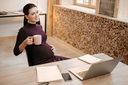 First pregnancy. Ambitious professional pregnant businesswoman carrying cup while posing at table and smiling Standard-Bild