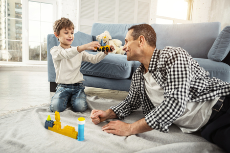 My favourite toy. Nice cheerful fair-haired boy playing with his erector set and his daddy sitting near him and playing with his son Stock Photo