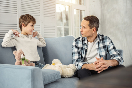 Family relationship. Handsome content young fair-haired boy smiling and sitting on the couch and talking with his daddy sitting near him