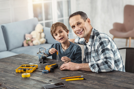 Loving daddy. Attractive cheerful dark-haired man showing instruments to his son while sitting at the table and his son holding compasses and smiling
