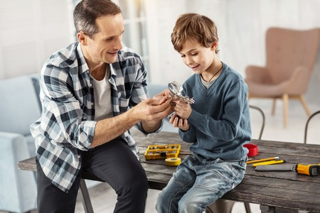 Happiness inside me. Attractive happy dark-haired father showing instruments to his son while sitting on the table and his son sitting near him Imagens