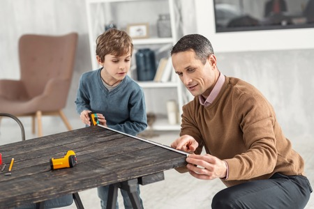 Sharing experience. Attractive curious little fair-haired boy holding a measuring tape and measuring the table and his daddy helping help