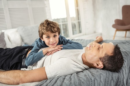 Nice delighted fair-haired boy smiling and his daddy while lying on his back on the sofa and they relaxing together