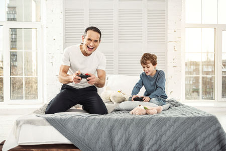 Playing games. Handsome exuberant well-built father smiling and playing games with his son and they holding remote controls 스톡 콘텐츠