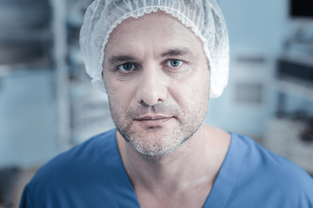 Im ready. Calm unshaken handsome patient being in the operational and looking straight focusing his view.
