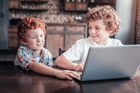 Modern generation. Positive cheerful nice boy sitting at the laptop and looking at his brother while spending time with him