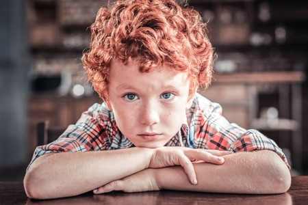 Young child. Nice pleasant red haired boy sitting at the table and putting his head on his hands while looking at you